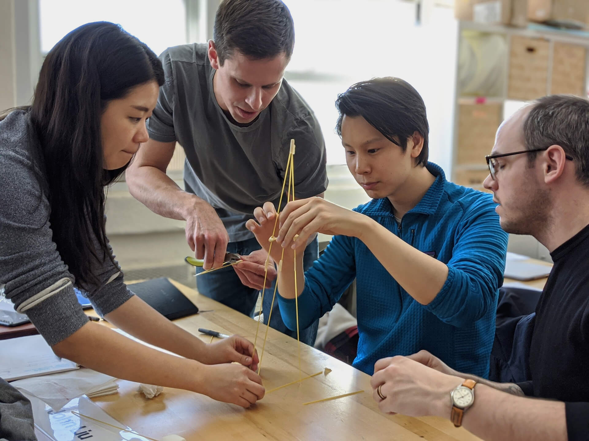 Allay team members building a spaghetti tower