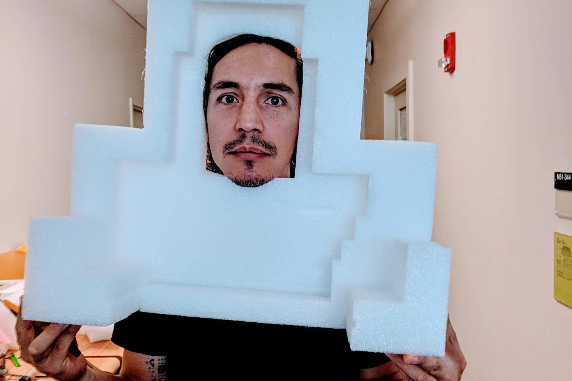 IDM student with their face peeking through a piece of styrofoam